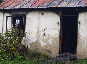 fragment spalonego domu. Widoczne okno oraz drzwi wejściowe do domu