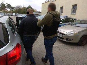 policjant doprowadza zatrzymanego mężczyznę